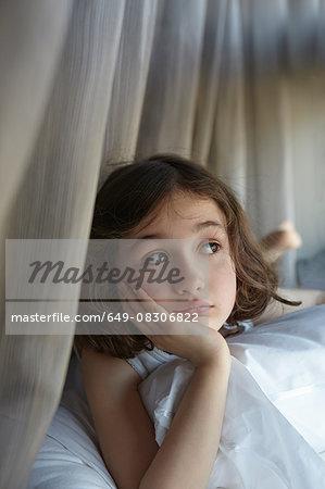 Girl reclining on bed gazing sideways