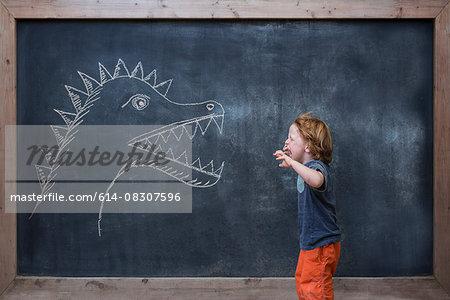 Young boy roaring at dinosaur drawing on blackboard
