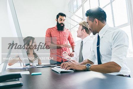 Business people in brainstorming meeting by office window