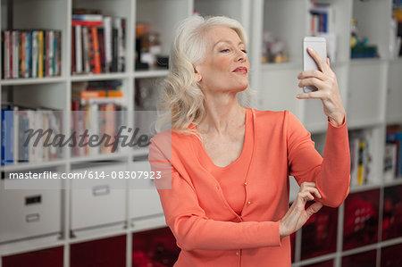 Mature woman taking self portrait, using smartphone, indoors