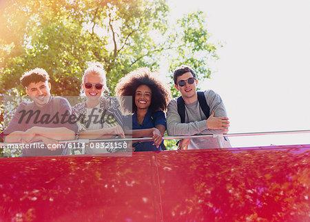 Portrait smiling friends riding double-decker bus