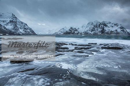 Snow covered mountains behind cold ocean, Vareid, Lofoten Islands, Norway