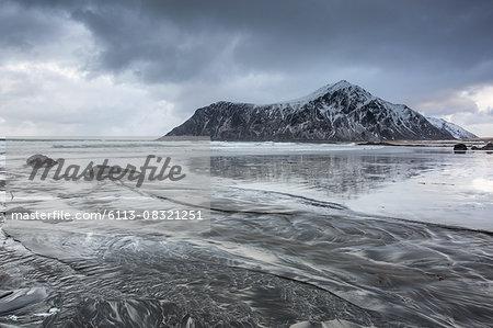 Snow covered rock formation on cold ocean beach, Skagsanden Beach, Lofoten Islands, Norway