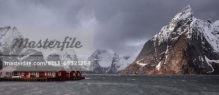 Snow covered mountain range above fishing village, Hamnoya, Lofoten Islands, Norway