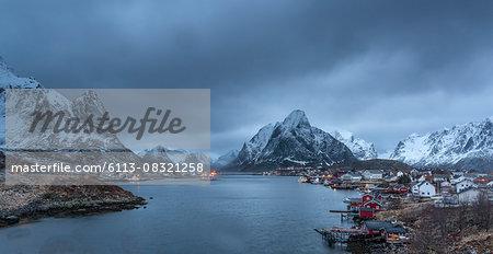 Snow covered mountain range above fishing village at dusk, Reine, Lofoten Islands, Norway
