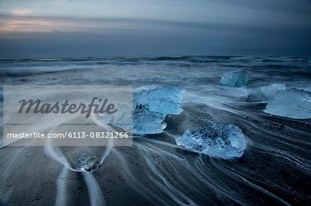 Long exposure of ice on cold stormy ocean beach, Jokulsarlon, Iceland