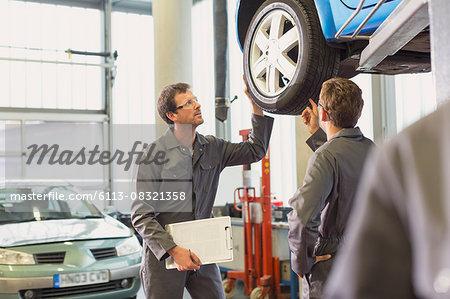 Mechanics examining and discussing tire in auto repair shop