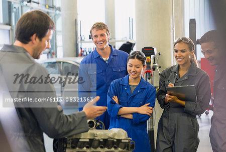 Mechanics discussing car engine in auto repair shop