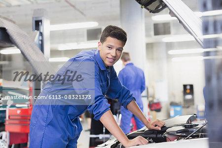 Portrait confident mechanic leaning over car engine in auto repair shop