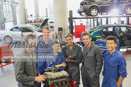 Portrait confident mechanics with car engine in auto repair shop