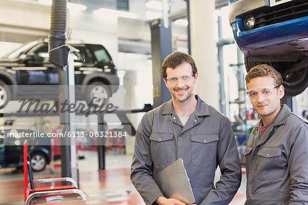 Portrait confident mechanics in auto repair shop