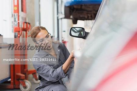 Female mechanic examining car in auto repair shop