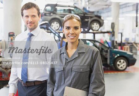 Portrait confident businessman and female mechanic in auto repair shop