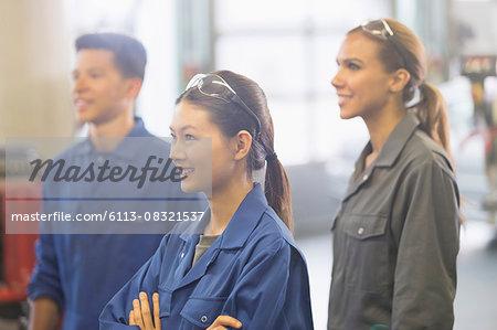 Smiling mechanics looking away in auto repair shop