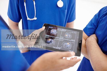 Doctors looking at scans on digital tablet