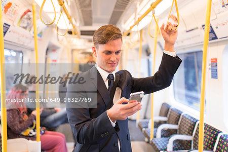 Businessman texting on tube, London Underground, UK