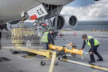 Ground crew fixing tow bar onto A380 aircraft at airport