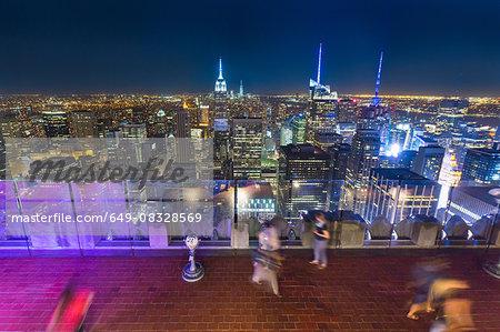 High angle view of midtown Manhattan and tourists at night, New York, USA