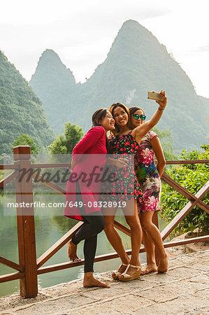 Three adult female friends posing for smartphone selfie at Li river, Yangshuo, Guangxi Zhuang, China
