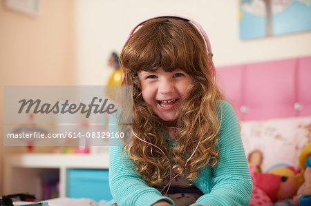 Portrait of girl in bedroom wearing headphones