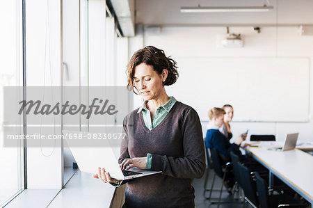 Professor using laptop in classroom