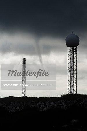 Radar tower on field against cloudy sky at dusk