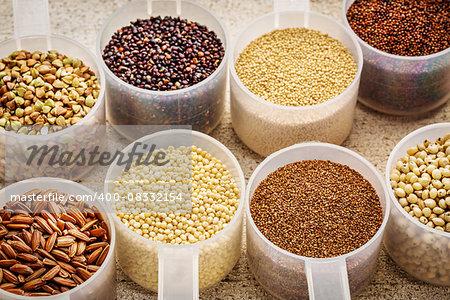 gluten free grains (quinoa, brown rice, kaniwa, amaranth, sorghum, millet, buckwheat, teff) - plastic measuring scoops on a rustic white painted barn wood