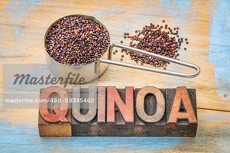 gluten free qunoa grain in a metal measuring scoop with a text in vintage letterpress wood type blocks