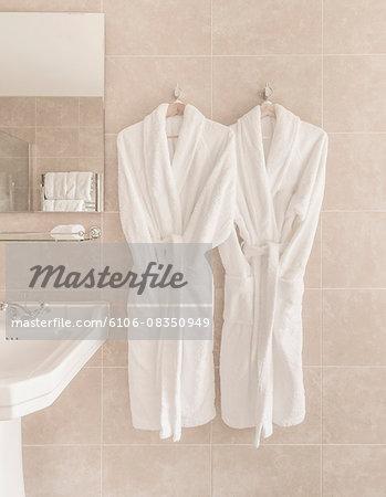 Two bathrobes hanging in bathroom