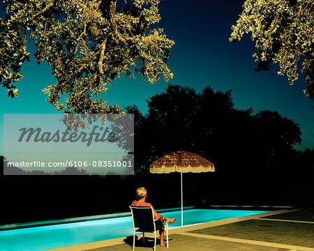 Men sitting by swimmingpool