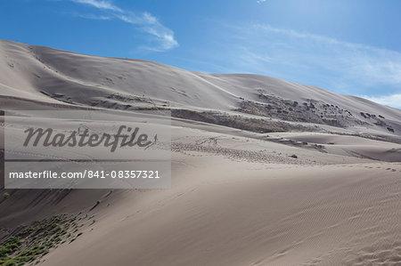 Distant people descending a huge sand dune, iridescent on a summer evening, Khongoryn Els, Gobi Desert, Mongolia, Central Asia, Asia