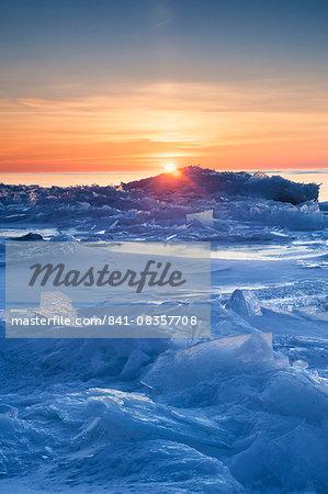 Orange sunrise on Lake Superior in winter illuminating plate ice on shore, Cascades region, North Shore, Minnesota, United States of America, North America