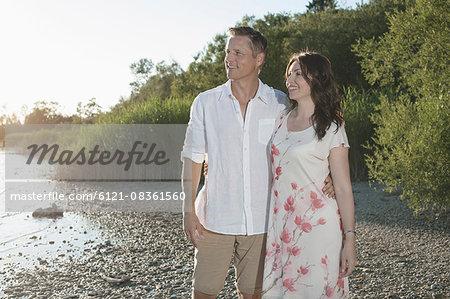 Mature couple smiling and looking at view at lakeside, Bavaria, Germany