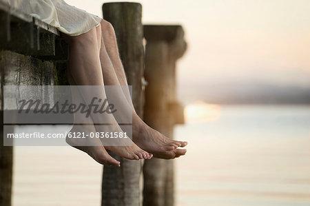 Couple legs dangling on pier, Bavaria, Germany