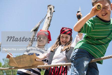 Children playing pirate game in adventure playground, Bavaria, Germany