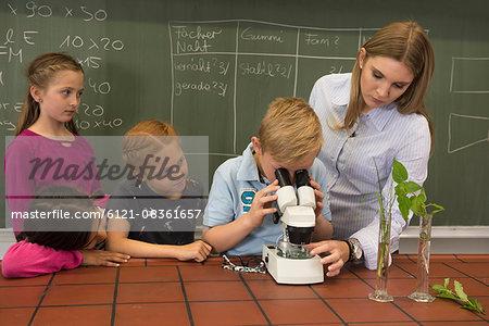 School students with teacher looking through a microscope, Fürstenfeldbruck, Bavaria, Germany
