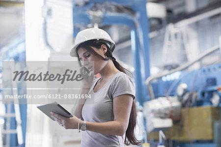Female engineer using a digital tablet and mobile phone in an industrial plant, Freiburg Im Breisgau, Baden-Württemberg, Germany