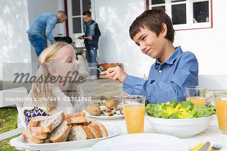 Teenage boy feeding sister at garden barbecue table
