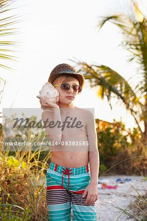 Portrait of boy listening to seashell at beach, Sanibel, Florida, USA