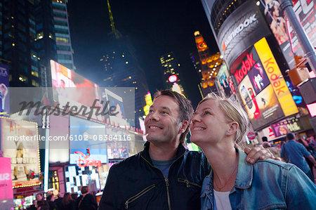 Couple at Times Square at night, New York City, USA