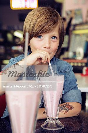 Happy boy with tattoos drinking milkshake