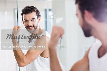Smiling man looking at his biceps in mirror