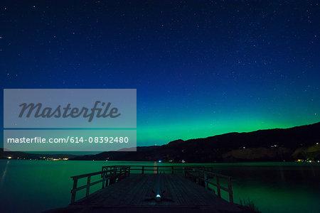 Man lying on pier star gazing at night, Wharf Park, Naramata, British Columbia, Canada