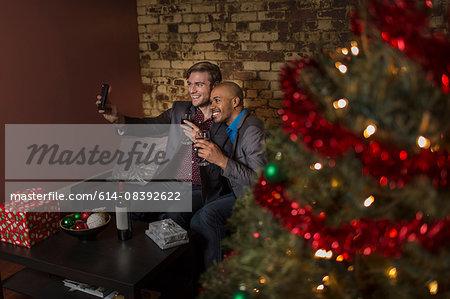 Male couple celebrating Christmas together, sitting on sofa, taking self portrait using smartphone
