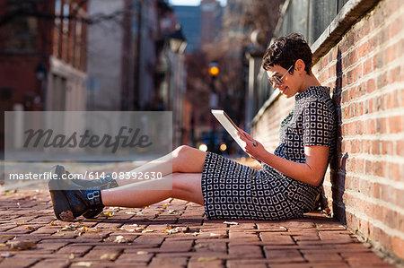 Mid adult woman sitting against brick wall, using digital tablet