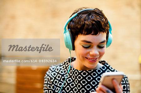 Mid adult woman, wearing headphones, looking at smartphone, smiling