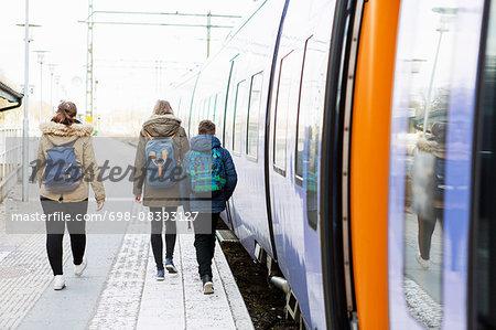 Rear view of high school students walking on railroad platform
