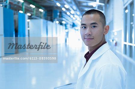 Portrait confident scientist in factory corridor