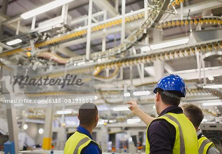Workers discussing winding printing press conveyor belts overhead