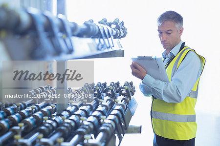 Engineer with clipboard checking printing press conveyor belt